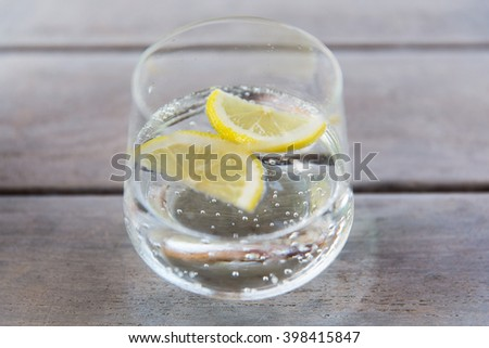 drink and refreshment concept - glass of sparkling water with lemon slices on table - stock photo
