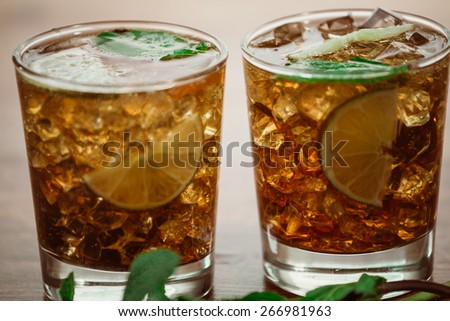 drink concept - cocktail with cola ice cubes and lime - stock photo