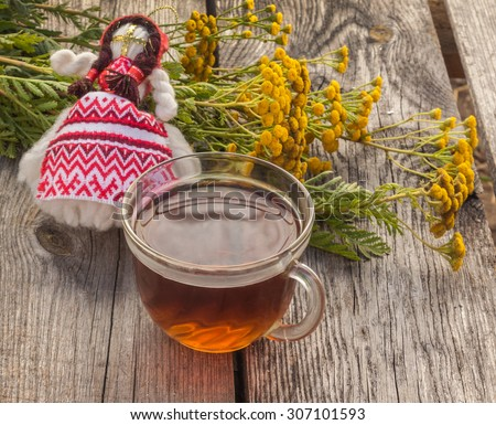 Drink from tansy and folk doll as the concept of traditional medicine - stock photo