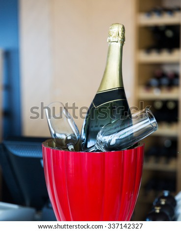 drink, holidays, celebration, alcohol and objects concept - close up of champagne bottle and glasses cooling in ice bucket at restaurant - stock photo