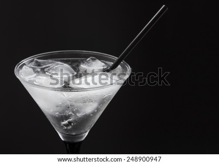 drink in a glass with ice and a cocktail tubes and fruits on a black background - stock photo