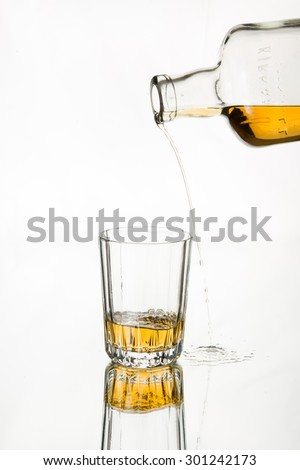 Drink responsibly; Drink aware; Don't drink and drive. Pouring whiskey missed the glass. Isolated, white background. Art in food and drink. - stock photo