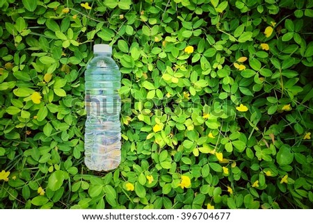 Drink water in bottles on green grass concept for freshness - stock photo