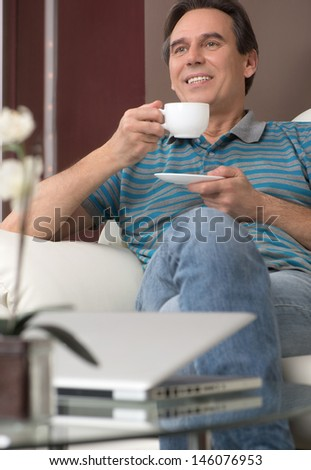 Drinking coffee at Sunday morning. Cheerful mature man sitting on the couch and drinking fresh coffee - stock photo