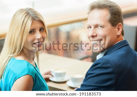 Drinking coffee together. Beautiful mature couple drinking coffee together and looking at camera while sitting in coffee shop - stock photo