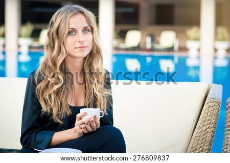 Drinking coffee. Young beautiful long hair woman holding cup while sitting at cafe near pool. - stock photo