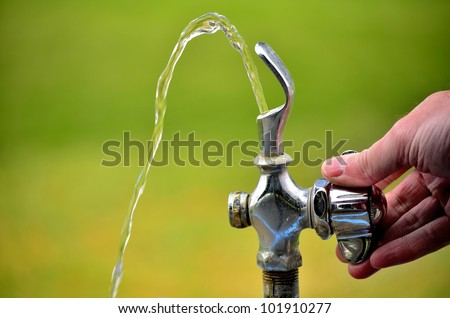 Drinking fountain in park with water flowing - stock photo