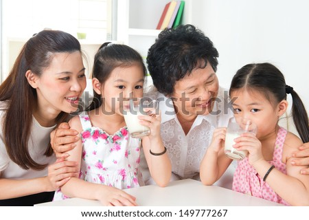 Drinking milk. Happy multi generations Asian family at home. Beautiful grandmother, mother  and granddaughters, healthcare concept. - stock photo