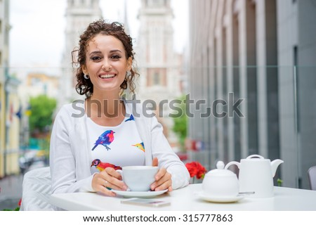 Drinking tea. Young beautiful brunette woman holding cup of beverage while sitting at cafe. - stock photo