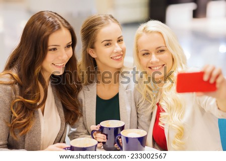 drinks, friendship, technology and people concept - happy young women with cups sitting at table and taking selfie with smartphone in cafe - stock photo