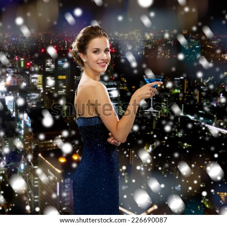 drinks, holidays, christmas, people and celebration concept - smiling woman in evening dress holding cocktail over snowy night city background - stock photo