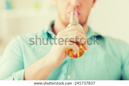 drinks, relax, leisure and people concept - close up of man drinking beer sitting on couch at home - stock photo