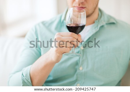 drinks, relax, leisure and people concept - close up of man drinking red wine and sitting on couch at home - stock photo