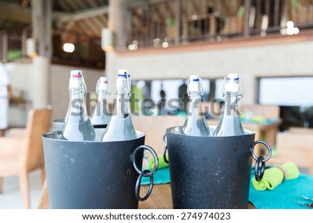 drinks, thirst, refreshment and summer resort concept - bottles of water in ice bucket at hotel restaurant - stock photo