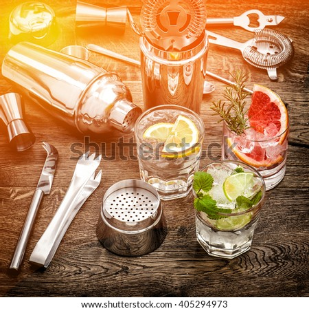 Drinks with ice and tonic water. Cocktail accessories. Vintage style toned picture with color lights effect - stock photo