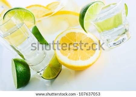 drinks with lemon and lime, shot on reflective white background. - stock photo
