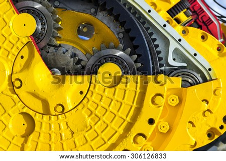 Drive gear and bearings, cross section of bulldozer sprocket internal mechanism, large construction machine with bolts and yellow paint coating, heavy industry, detail  - stock photo