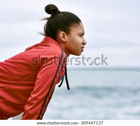 Driven young woman dressed in a red jacket looking out into the distance as she rests and catches her breath after taking a morning run to try and lose weight - stock photo
