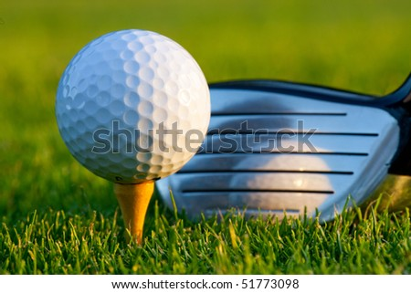 Driver behind gold ball on golf course - stock photo