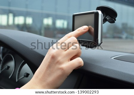 Driver entering an address into the navigation system - stock photo