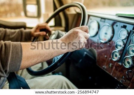 driver hands holding steering wheel - stock photo