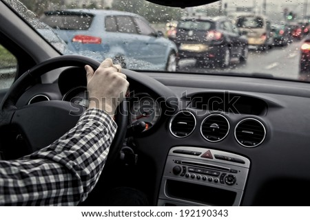 driver in traffic on a cloudy and rainy day - stock photo