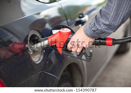 Driver inserting pumping nozzle with gasoline at the gas station - stock photo