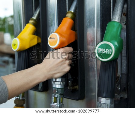 Driver pumping gasoline at the gas station - stock photo