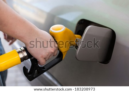 Driver pumping gasoline at the gas station, closeup - stock photo