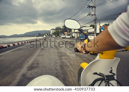 Driver riding motorcycle on an asphalt empty road near sea. Adventure and vacations concept.
