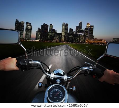 Driver riding motorcycle on an asphalt road at night towards big city - stock photo