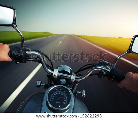 Driver riding motorcycle on an empty asphalt road - stock photo