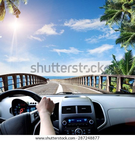 Driver's hands on a steering wheel of a car and blue sky with clouds - stock photo