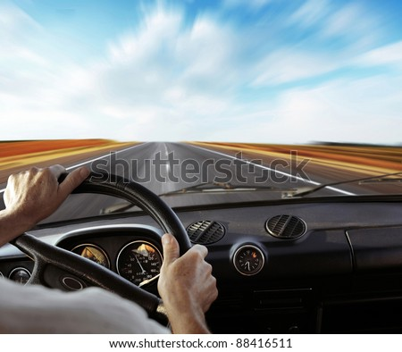 Driver's hands on a steering wheel with motion blurred road and sky - stock photo