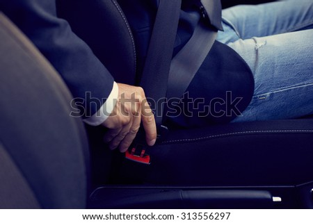 Driver sits in the car and fastens his seat belt, toned - stock photo