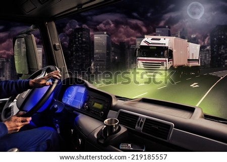 driver view from the cockpit of a truck on the road by night - stock photo