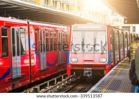 Driverless urban trains at station in London. There are two trains, one on background and another one arriving. Transport and technology concepts - stock photo