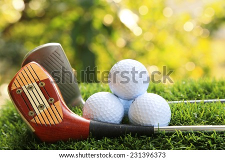 Drivers and golf balls on green grass - stock photo