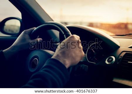 Driving a car at sunset - focus on steering weel - stock photo