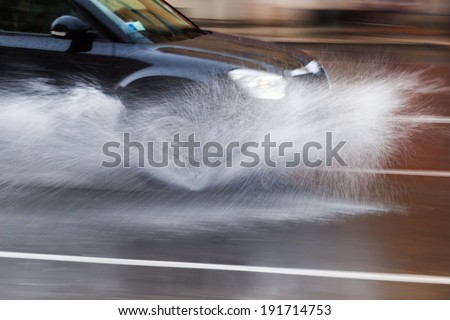 driving car on a wet street with splashing water in motion blur - stock photo