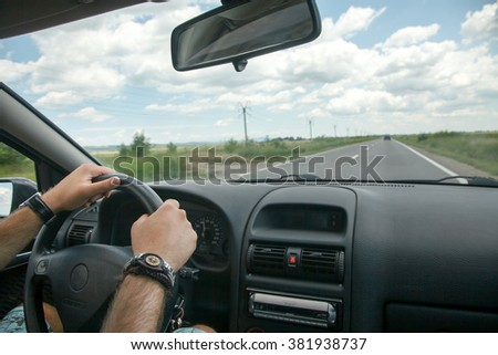 Driving concept  driver hands on wheel and car on road - stock photo