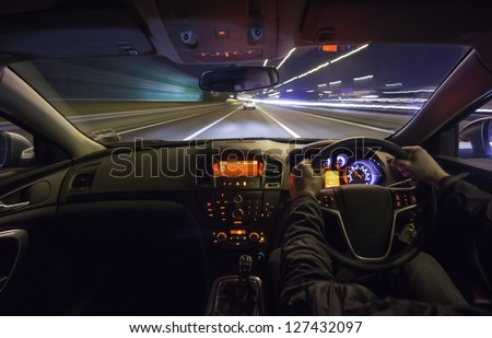 Driving fast after a car on motorway at night. - stock photo