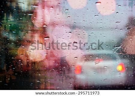 Driving in rain, raindrops on car window with light bokeh, rainy season abstract background. - stock photo
