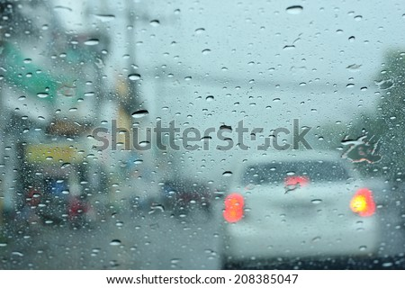 Driving in rain, Road view through car window with rain drops. - stock photo
