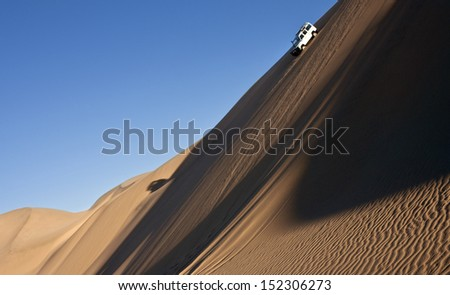Driving in the sand dunes of the Namib Desert near Sandwich Bay on the coast of Namibia - stock photo