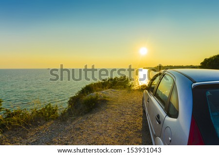 Driving into the sunset, Driving sport car and rear view mirror into the sunset with the countryside sea water horizon rolling by on a summer day. concept for business, speed or success - stock photo