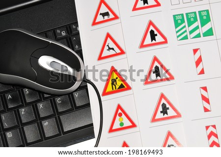 Driving licence online concept with computer and traffic signs - stock photo