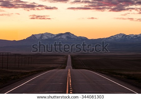 Driving on a long lonesome western highway into snow capped mountains. - stock photo