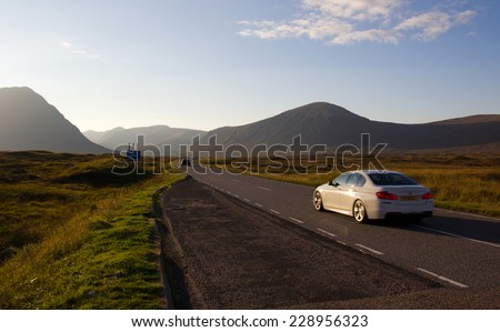 Driving on a road in the scottish highlands during sunset - stock photo