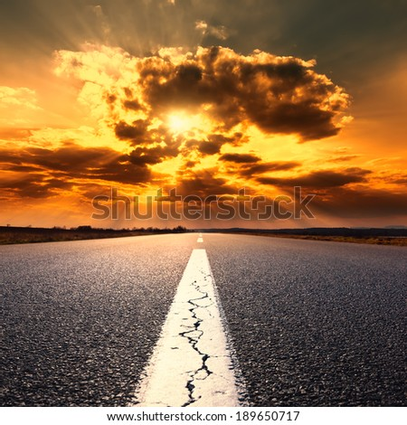 Driving on an empty asphalt road at sunset - stock photo